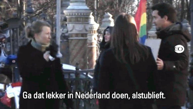 Presentator Manuel Venderbosch in Rusland met een regenboogvlag en een bord met een pro-homoslogan. Beeld EO