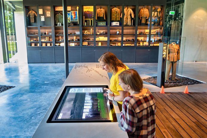 en Wanda Smigielski (voorgrond) en Wendy Dujardin kijken in het Generaal Maczek Memorial naar foto's van toen en nu. In de vitrines is een deel van de collectie van het voormalig museum te zien.
