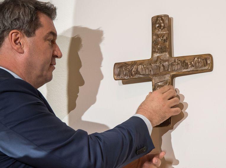 Minister-president Markus Söder (CSU)van Beieren hangt onder het oog van de verzamelde media een kruis op in de Münchener staatskanselarij. Beeld AFP