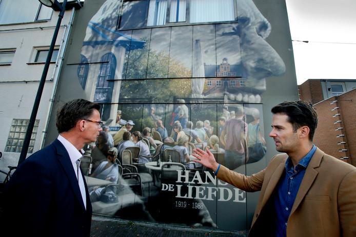 Wethouder Harry van Waveren (links) en centrummanager Sem den Hollander bij het portret van Hans de Liefde, de sportgrondlegger van Oud-Beijerland.