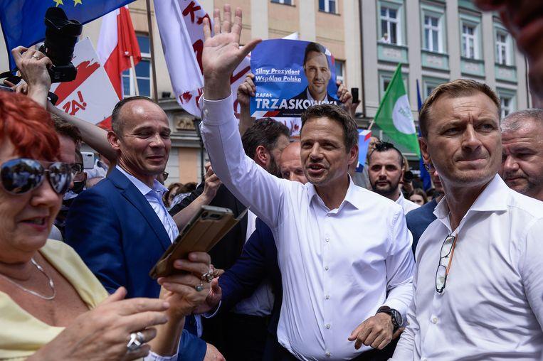Rafal Trzaskowski (midden), de huidige burgemeester van Warschau, tijdens een campagnebijeenkomst. Het verschil met Duda in de peilingen is kleiner dan de foutmarge. Beeld Getty Images