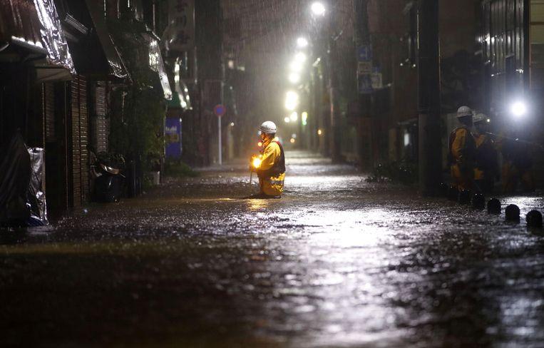 Brandweerlieden inspecteren een ondergelopen straat in de wijk Ota van Tokio. Foto JAPAN OUT. Beeld null