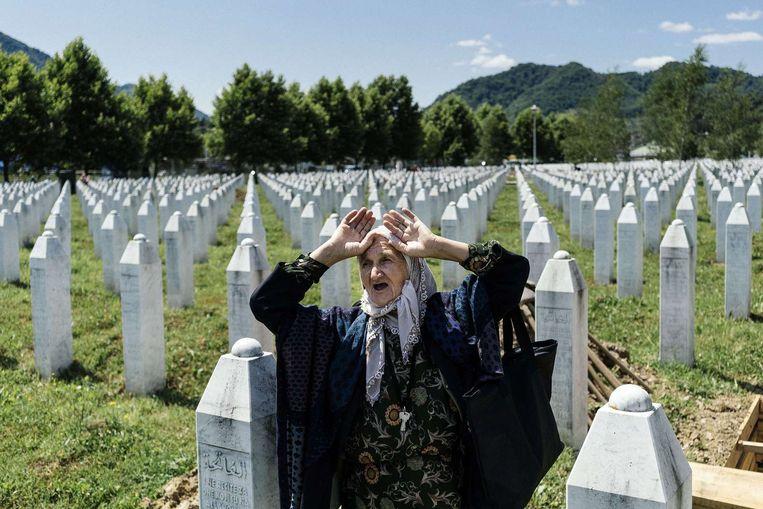 Een Bosnische vrouw knielt voor het graf van een familielid bij de Potocari Memorial Center vlakbij Srebrenica. Beeld afp