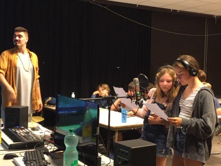 Odil (rechts) en Christina zingen hun stukje rap in voor de microfoon. Links kijkt muzikant Owen Perry Weston goedkeurend toe.