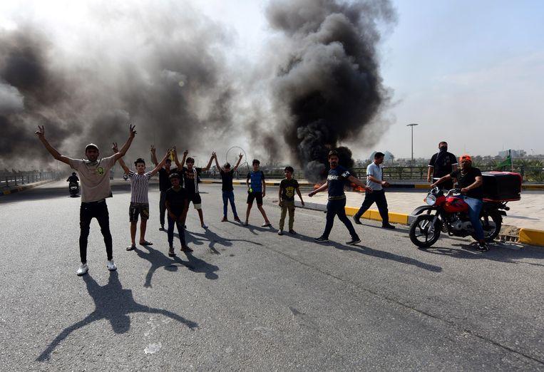 Iraakse betogers zetten autobanden in brand in Bagdad, eerder deze maand. Beeld EPA