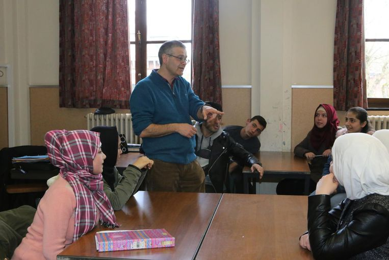 """Jan Enkels tussen zijn leerlingen in de OKAN-klas. """"Liever dan het leven naar de klas te brengen, ga ik met de leerlingen naar het leven toe."""""""