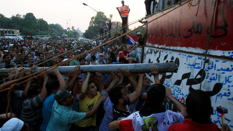 Betogers in Caïro probeerden op 9 september vorig jaar een betonnen muur omver te krijgen die was opgetrokken nabij de Israëlische ambassade. Beeld REUTERS