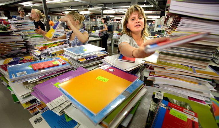 Bij Van Dijk Educatie worden door vakantiekrachten boekenpakketten samengesteld voor het komende schooljaar.  Beeld ANP