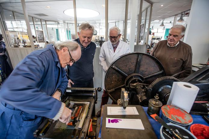 De oud-medewerkers van Drukkerij/Uitgeverij Helmond Eric van Kilsdonk, Cees Verschuur en Jan Balvers (vlnr) kijken hoe een boekenlegger wordt gedrukt.