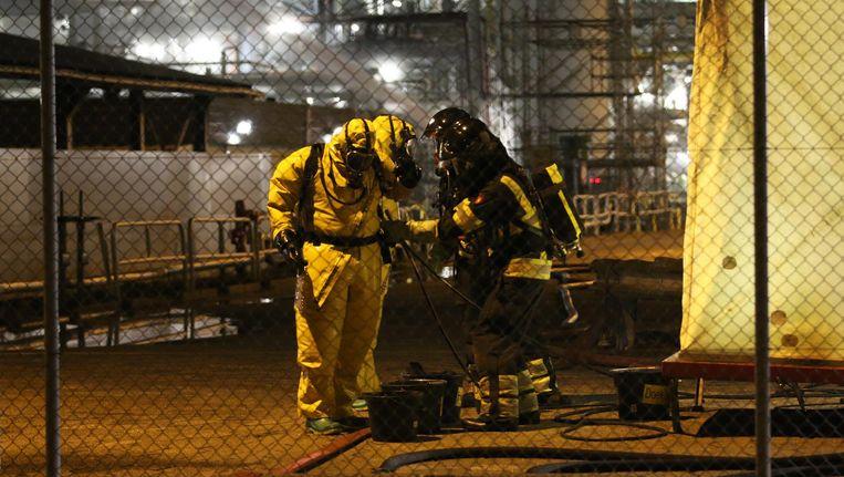 Medewerkers van Shell en de brandweer aan het werk bij de fabriek. Beeld anp