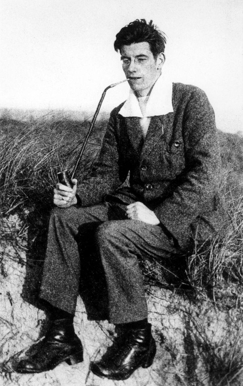 Schrijver, dichter, scheepsarts Jan Jacob Slauerhoff rookt een pijp in de duinen op Vlieland tijdens een vakantie als student. Waddeneilanden, Nederland, ca. 1919. Beeld Nationaal Archief/Collectie Spaarnestad