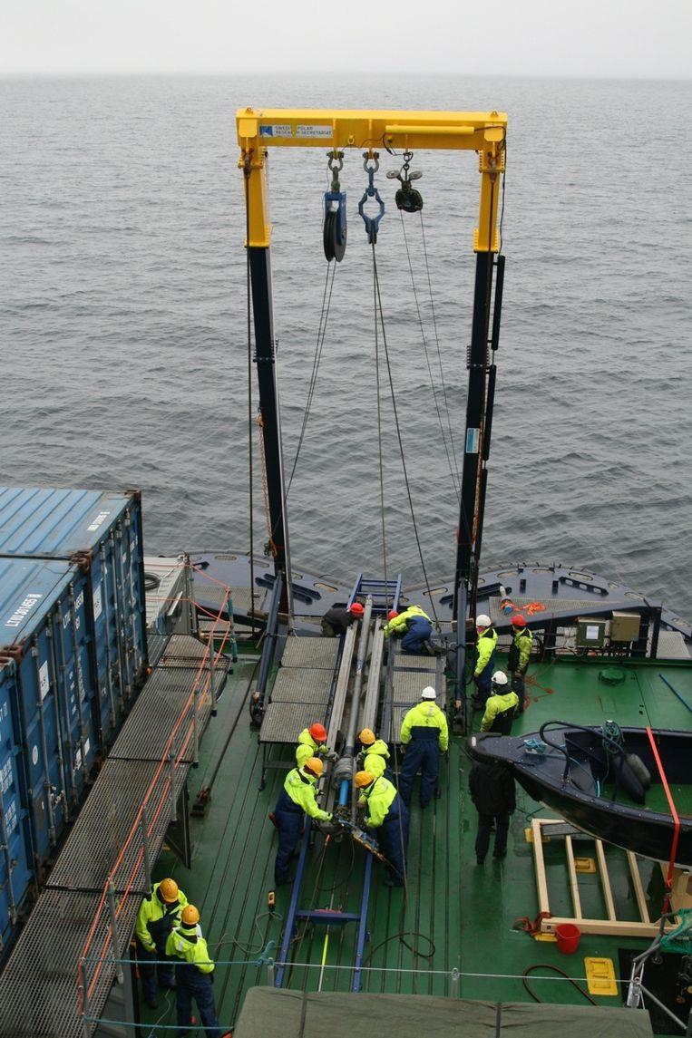 Het instrument waarmee monsters uit de zeebodem worden genomen, wordt te water gelaten. Beeld Jorien Vonk