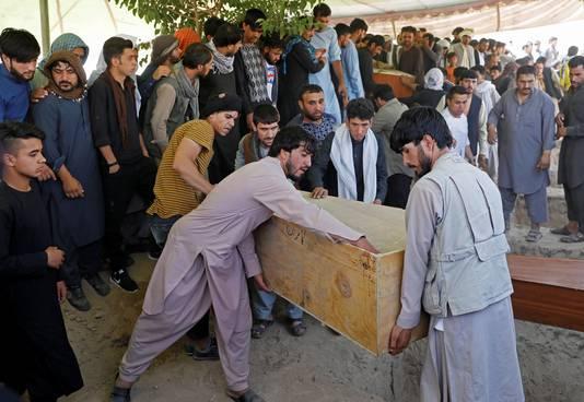 Mannen dragen een doodskist met daarin een van de slachtoffers van de bomaanslag op de bruiloft in Kaboel.