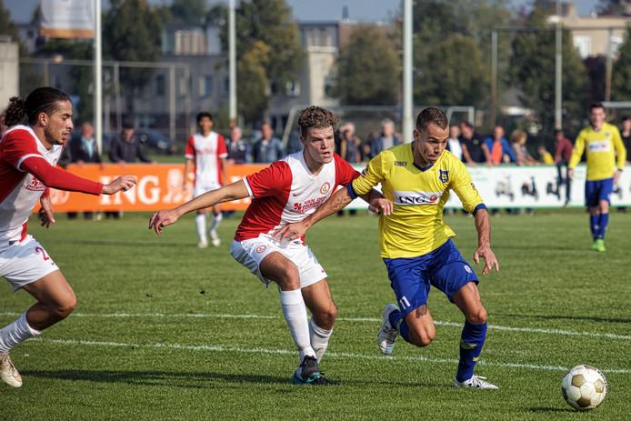 Dongen-speler Jorik Mijnhijmer passeert DESO-speler Martijn vd Rijdt. Geheel links komt DESO speler Abdel-llah Aziz te hulp gesneld.