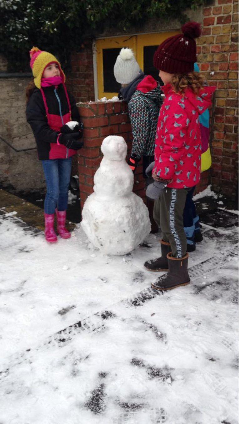 Deze meisjes houden het bij het maken van een sneeuwpop
