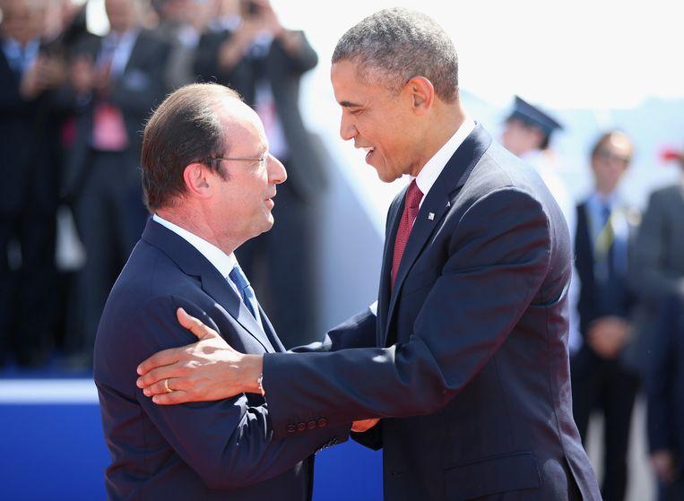 Francois Hollande(L)schudt Barack Obama de hand Beeld getty