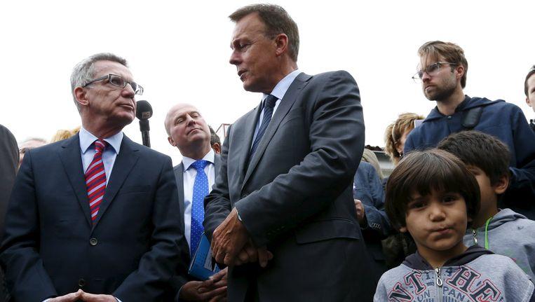 De Duitse minister van Binnenlandse Zaken Thomas de Maiziere (links) en Thomas Oppermann, de fractieleider van de Duitse SPD (rechts) tijdens een bezoek aan het vluchtelingenkamp in Friedland, Duitsland. Beeld REUTERS
