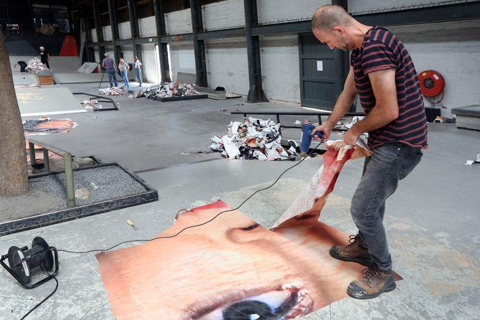 Vrijwilligers van BredaPhoto verwijderen de beelden van de vloer van skatehal Pier15.