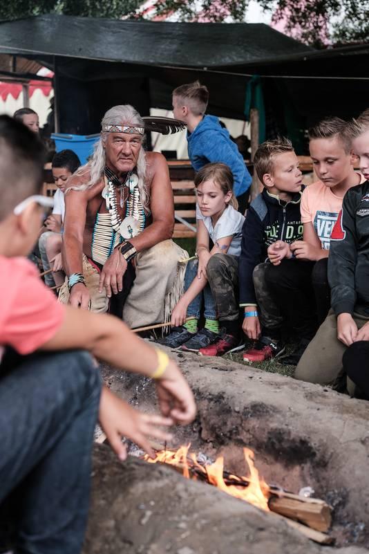 De 'echte indiaan' van het bouwdorp in Zevenaar helpt de kinderen met brood bakken boven een vuurtje.