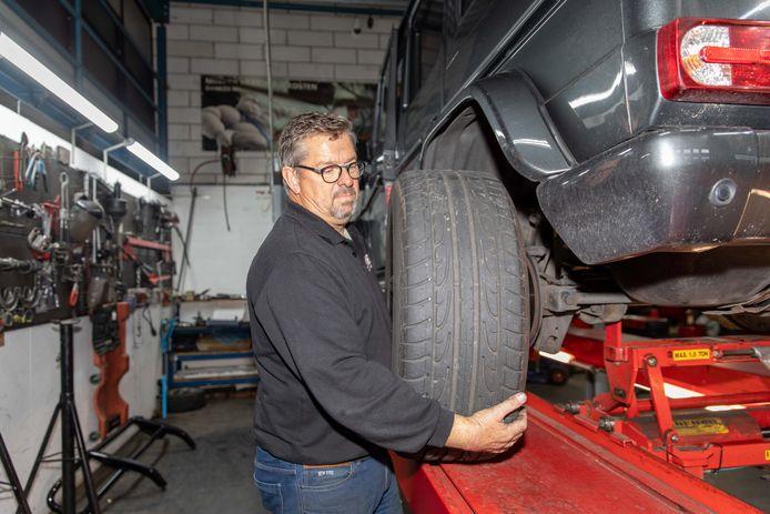 Martin van Riet bezig met de halfjaarlijkse bandenwissel bij een Mercedes terreinauto.