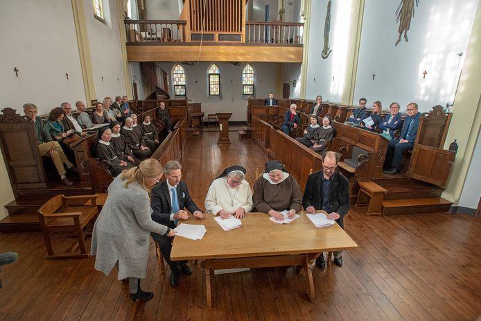 Vlnr aan de ondertekeningstafel: wethouder Van der Schoot, zr. Sara (KNR), abdis Angela en gedeputeerde Henri Swinkels.  Links provinciewoordvoerster Karen Pleunis, die de bijeenkomst presenteerde.