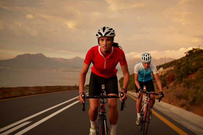 Professional female cyclists on road bikes at sunset