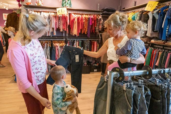 Vrijwilligster Elise Cornelisse (rechts) helpt haar dochter Judea de Koster en kleinkinderen Thijs en Lize met het uitzoeken van kleding.