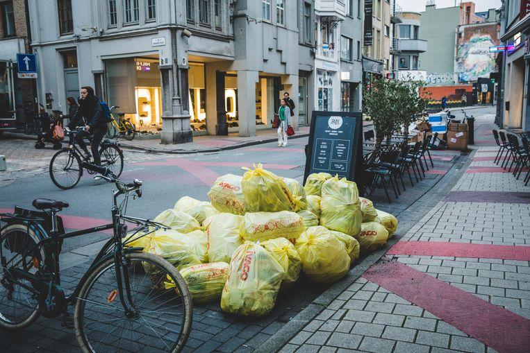 Een hoop vuilniszakken aan de terrassen in de Walpoortstraat.