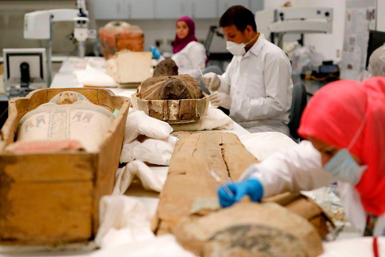 Egyptische archeologen zijn in het Egyptisch Museum in Cairo bezig met het restaureren van de mummie en de sarcofaag van Toetanchamon. Het is de eerste keer sinds de vondst van het graf van de Egyptische koning in 1922 dat diens lichaam vanuit de Vallei der koningen in Luxor naar Cairo is overgebracht.  Beeld AFP