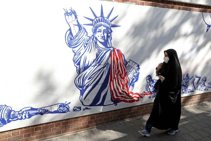Een vrouw loopt in Teheran voorbij de voormalige VS-ambassade.