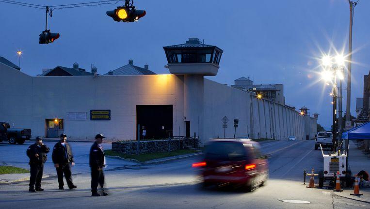Bewaarders staan voor de met 9 meter hoge muren omheinde Clintongevangenis in Dannemore. Twee van de wachttorens waren onbewaakt tijdens de ontsnapping Beeld ap