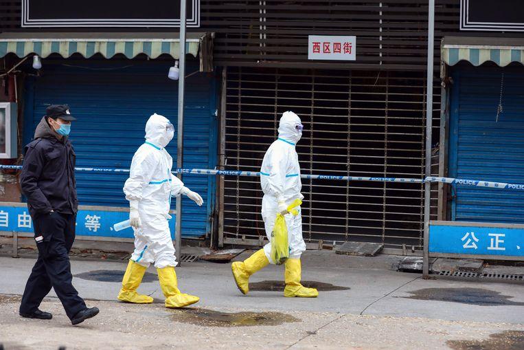 Geen marktkooplui op de grootste voedselmarkt van Wuhan, maar politiemannen en mensen van de ontsmettingsdienst.  Beeld AP