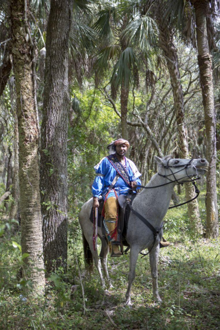 Een ruiter te paard in Seminole-kostuum tijdens het naspelen van een van de 19de-eeuwse veldslagen tegen de witte kolonisten, in de bossen bij Immokalee. Beeld Chantal Heijnen