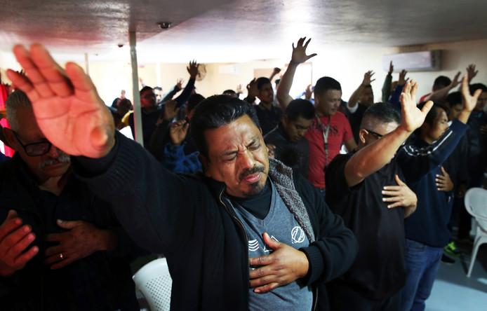 Evangelisten doen hun handen in de lucht als teken van gebed voor Christina Langford Johnson.