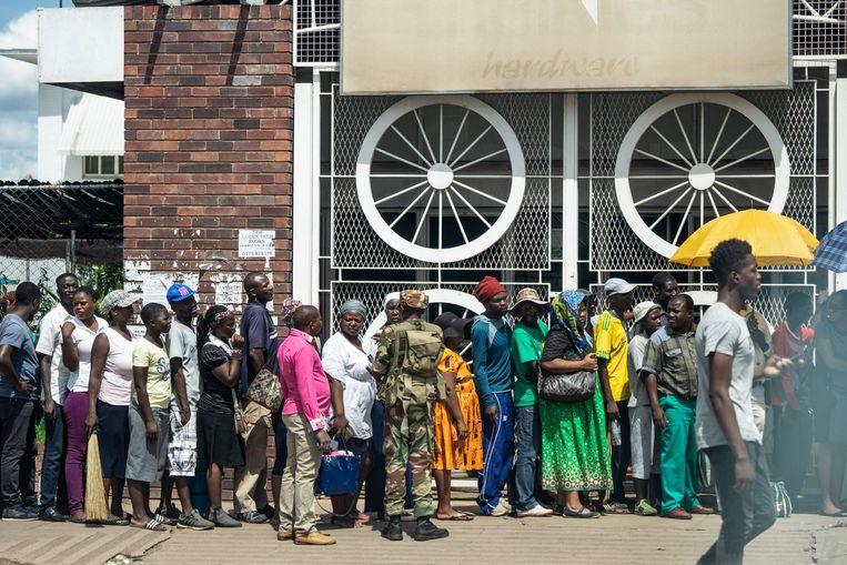 Onder toezicht van veiligheidstroepen staan mensen in de rij voor een supermarkt in de hoofdstad Harare.  Beeld AFP