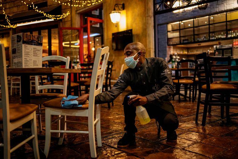 Een ober ontsmet een stoel in een restaurant in Johannesburg, Zuid-Afrika.