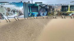 Kusttram en auto's zitten vast in het zand. Tramlijn onderbroken