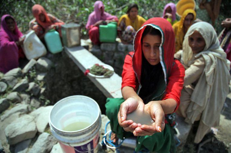 Een vrouw toont het vervuilde water dat ze te drinken krijgen in Kashmir. Beeld EPA