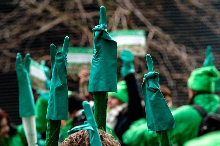 De poetshulpen staken bij de vorige actie onder meer een symbolische middelvinger op via de handschoenen op hun paraplu's.