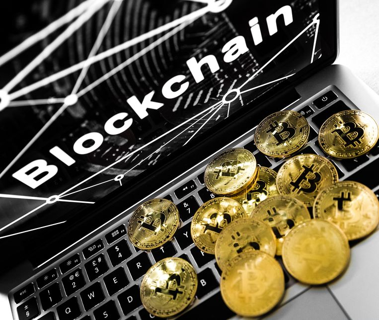 De cryptovaluta Bitcoin en een laptop met het woord blockchain, de technologie achter de Bitcoin.