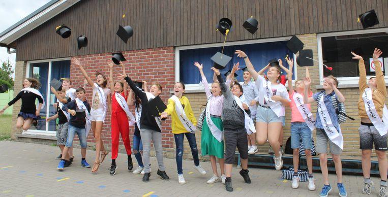 De leerlingen van het zesde leerjaar van de Vrije School Ruien gooien de afstudeerhoedjes in de lucht.