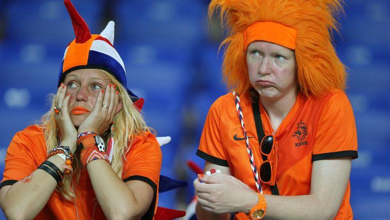 Teleurgestelde supporters na de verloren wedstrijd van het Nederlands elftal tegen Duitsland, op het EK van 2012. Nederlanders gaven dat jaar ongeveer 60 miljoen euro uit aan oranjeartikelen. Beeld anp