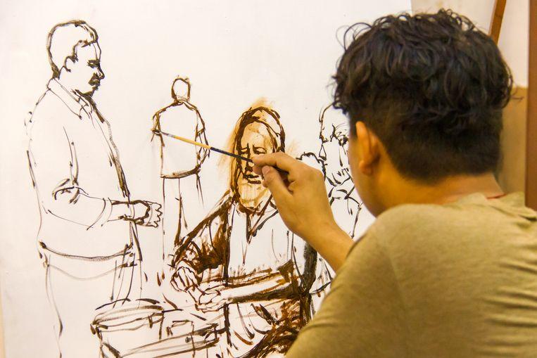 Een Nepalese uitwisselingsstudent schildert in snelle streken een groep mensen. Beeld null