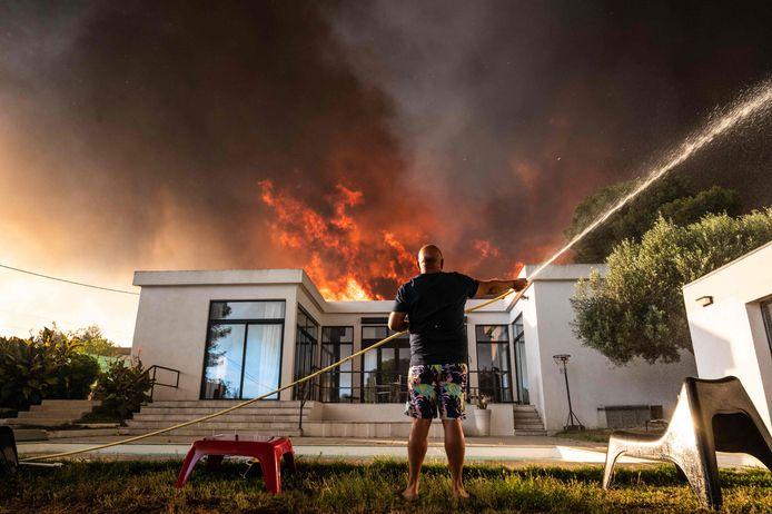 Een man houdt zijn woning nat in La Couronne, nabij Marseille.