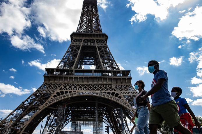 Mensen met mondmasker aan de Eiffeltoren.