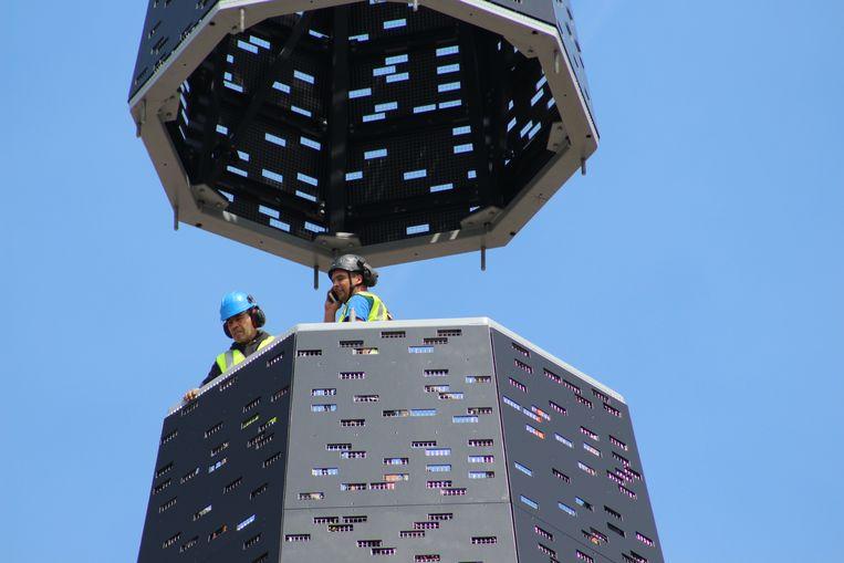 In de torenspits zelf vatten arbeiders post op een stelling. Telkens wanneer er een nieuw stuk geplaatst werd, mochten zij aan de slag. Je ziet ook de ingebouwde ledverlichting.