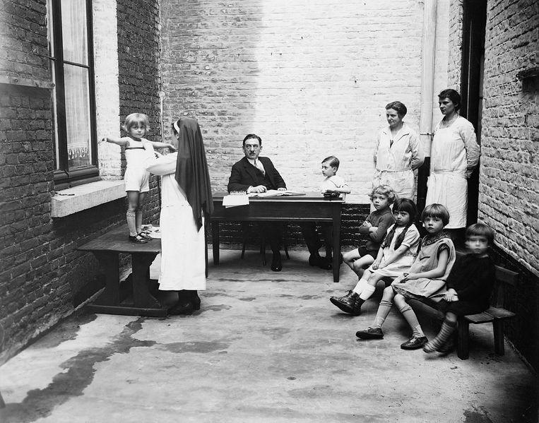 Een consult in Charleroi begin jaren 1900, vóór de officiële oprichting. De zuster meet, de man aan het bureau noteert.