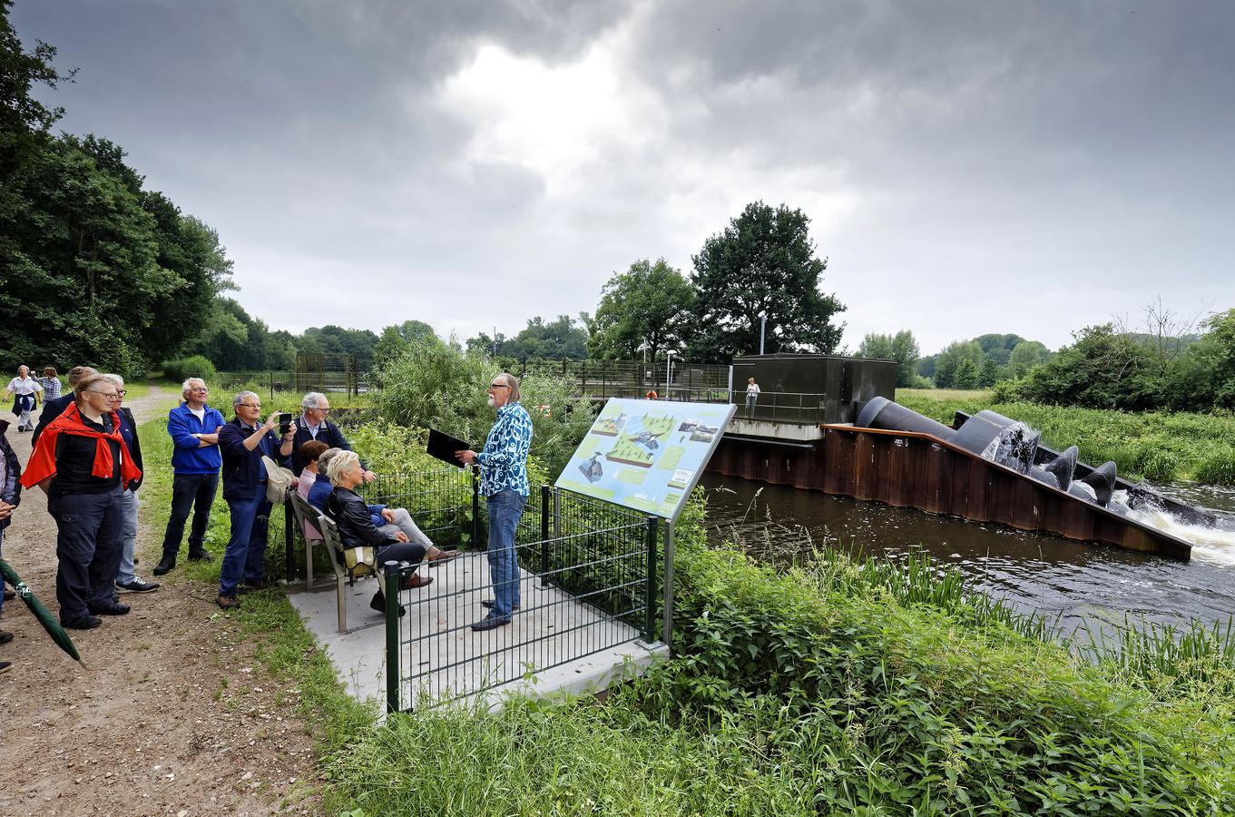 Onthulling van bankje en infobord bij waterkrachtcentrale in de Dommel in Sint- Michielsgestel. Gé van Berkel draagt een gedicht voor.