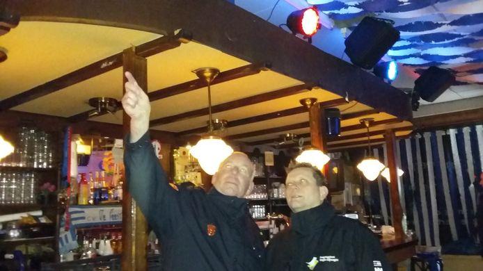 Namens de brandweer neemt Ben Maassen (links) de feestversiering in 't Nimweegs Feestcafé aan de Bloemerstraat onder de loep.