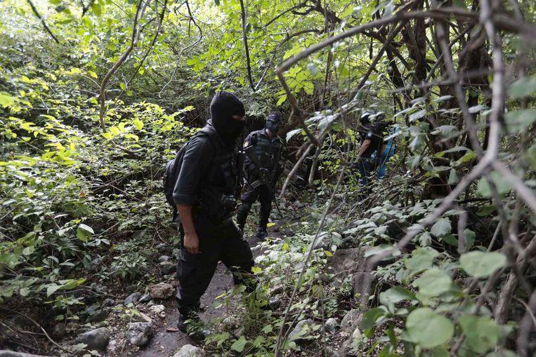 Militairen in de buurt van het massagraf. Beeld reuters